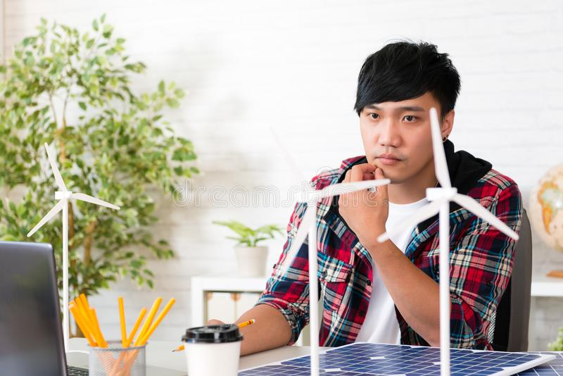 Asian man wind power engineer looking windmill royalty free stock photo