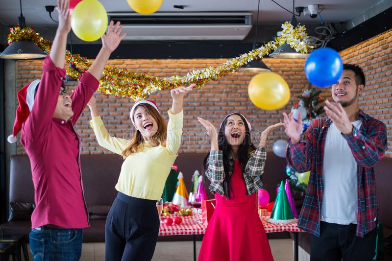 Asian man and woman having fun in Christmas party, dancing and playing balloons at the restaurant. Asian men and women having fun in Christmas party, dancing and royalty free stock photos
