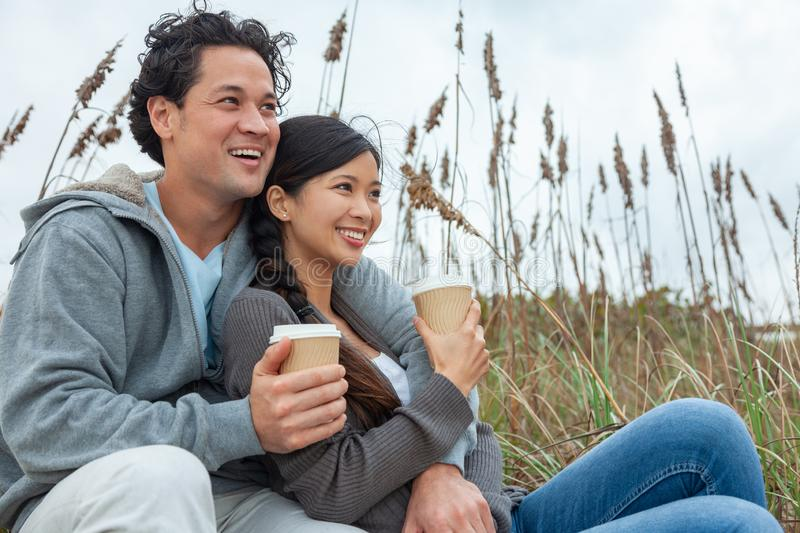 Asian Man Woman Romantic Couple Drinking Takeout Coffee on Beach. Young Asian Chinese men and woman, boy girl, couple with perfect teeth sitting on a beach royalty free stock photos