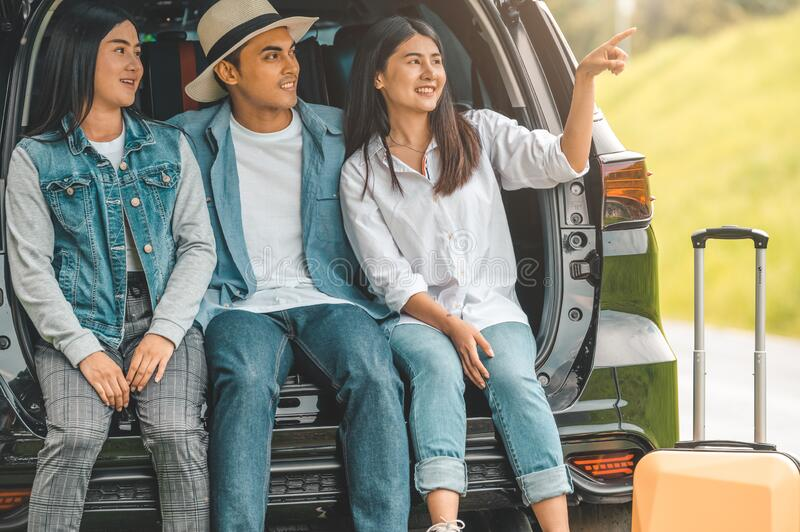 Asian man and women relaxing in back of car trunk during travel in summer. Transportation and people lifestyles concept. Group of. Asian men and women relaxing stock images