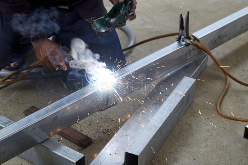 The welders are welding steel in the factory. Asian man worker making sparks while welding steel royalty free stock photo