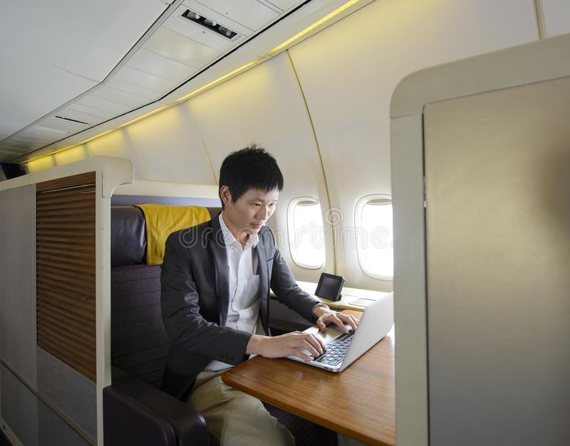 Asian man working with laptop on first class airplane.  royalty free stock photography