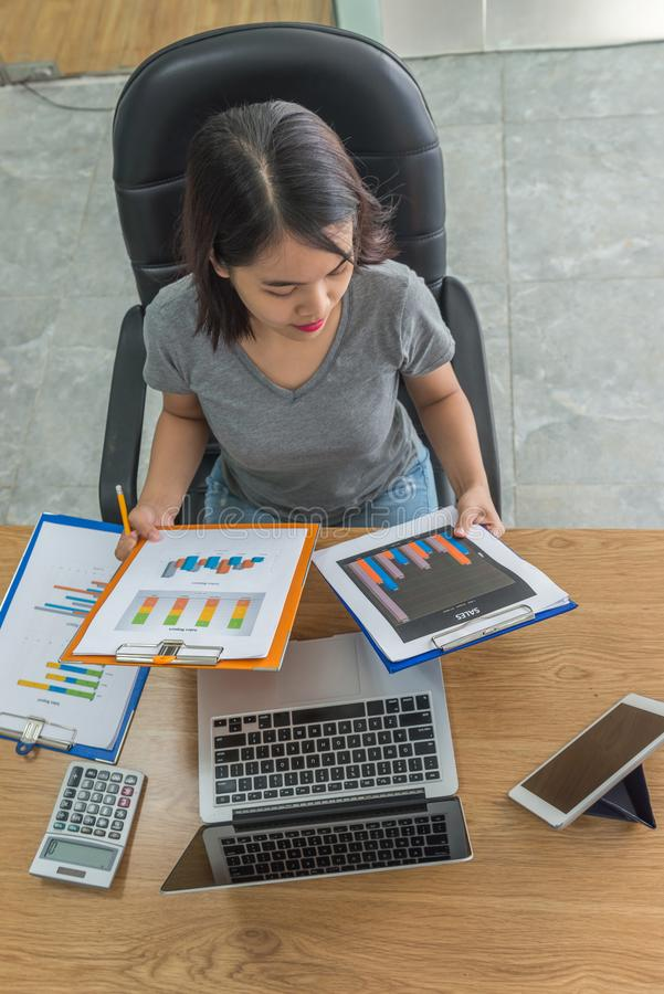 Asian manager checking sales reports in her business office royalty free stock photography