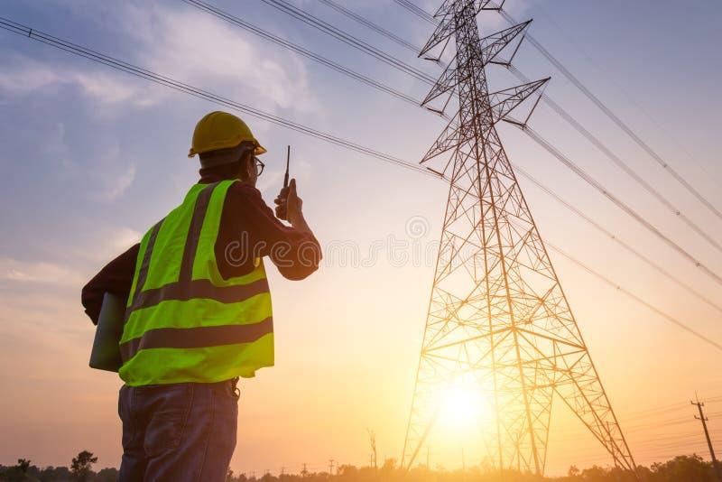 Asian Manager Engineering in Standard-Sicherheits-einheitliches Arbeiten überprüft die Hochspannungsmasten stockfoto