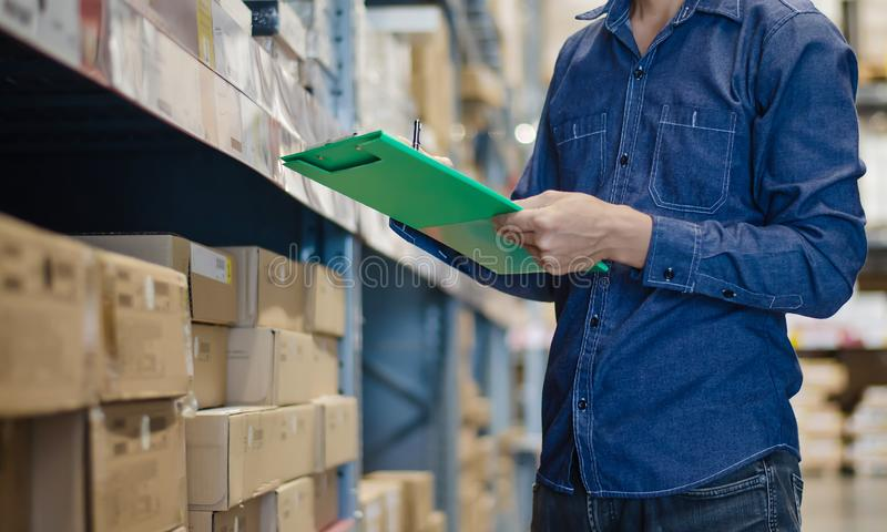 Asian manager man doing stocktaking of products management in cardboard box on shelves in warehouse using clipboard file and pen. royalty free stock images