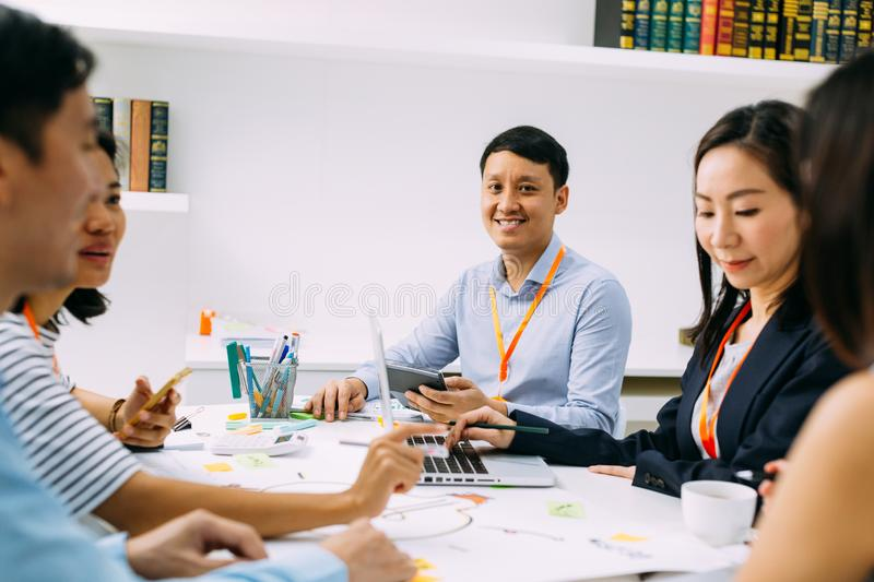 Asian mature business man smiling and looking at camera while sitting in meeting with other business men and women stock images