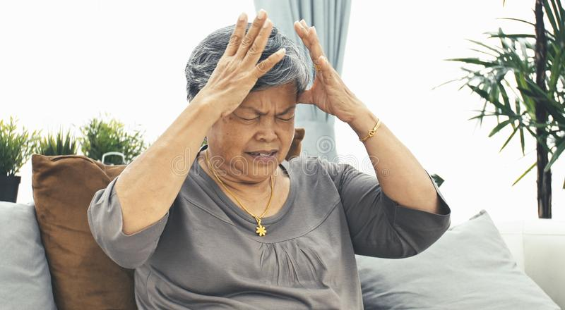Asian Mature woman with elderly woman with headache takes a pill.  royalty free stock images