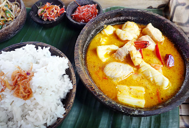 Asian meal - Sea food curry with rice. A delicious southeast asian lunch of spicy seafood curry served with steamed white rice and side dishes of vegetables and stock photos