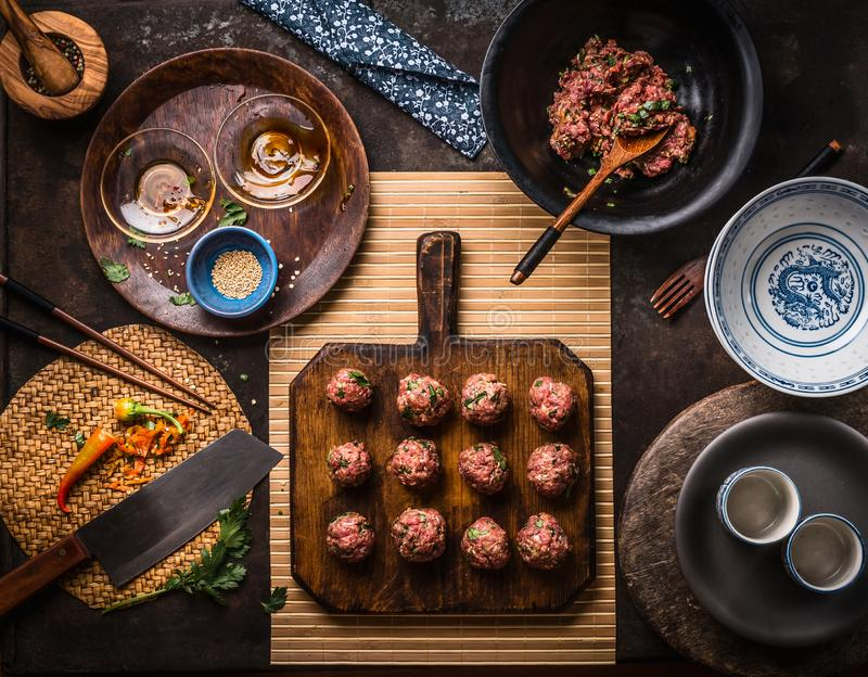 Asian meat balls on wooden cutting board with ingredients, kitchen utensils, bowls and plates, top view. Asian cuisine concept. Asian meat balls on wooden stock images