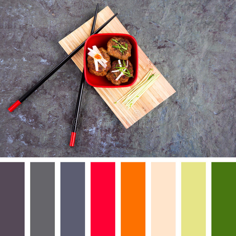 Asian meatball palette. Asian meatballs, garnished with pea shoots and radish julienne, in a red bowl on bamboo tray with chopsticks. In a colour palette with stock images