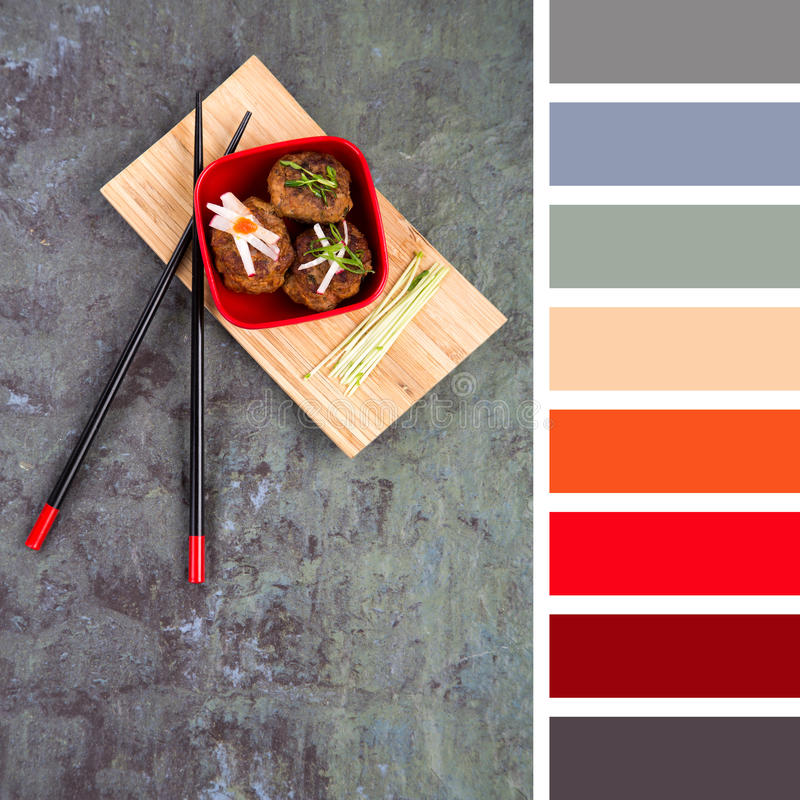 Asian meatball palette. Asian meatballs with vegetable garnishes in a bowl, over a bamboo tray with read and black chopsticks. In a colour palette with royalty free stock images