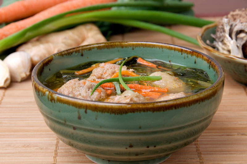Asian Meatball Soup. Bowl of Asian pork meatballs with vegetables in a clear broth sitting on a bamboo mat. Ingredients including ginger, garlic, green onions royalty free stock images