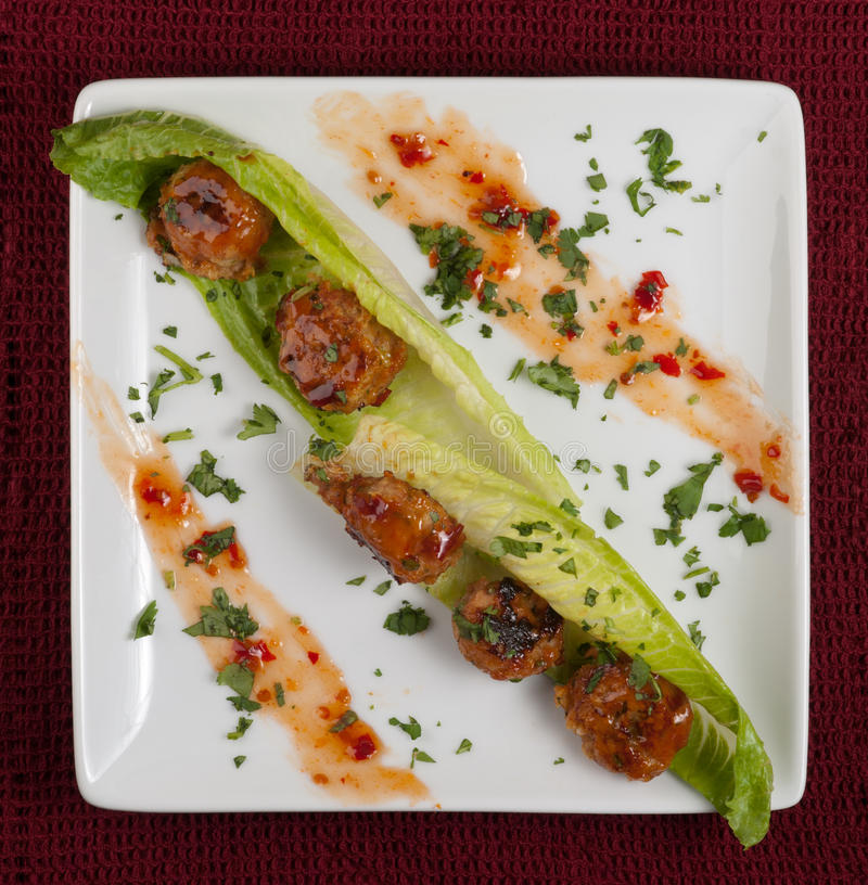 Asian meatballs. And red chile sauce on lettuce royalty free stock photography