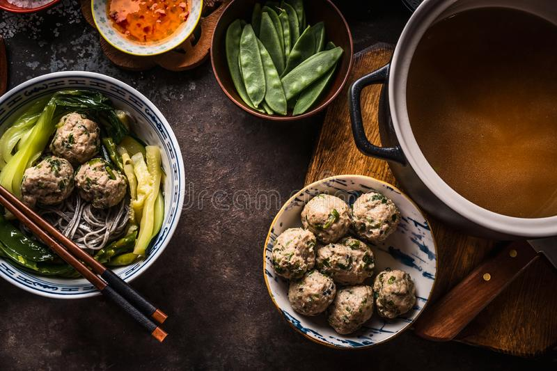 Asian meatballs and bowl with noodle soup on dark rustic background with ingredients, top view. Asian cuisine royalty free stock photos