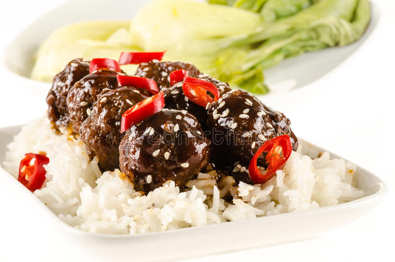 Asian meatballs with chinese sauce. Served with rice, steamed bok choy royalty free stock images