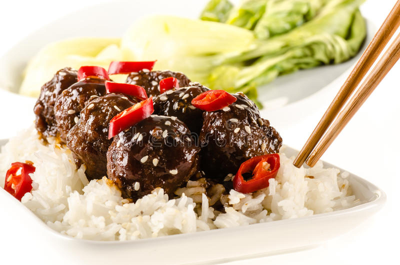Asian meatballs with chinese sauce. Served with rice, steamed bok choy royalty free stock photos