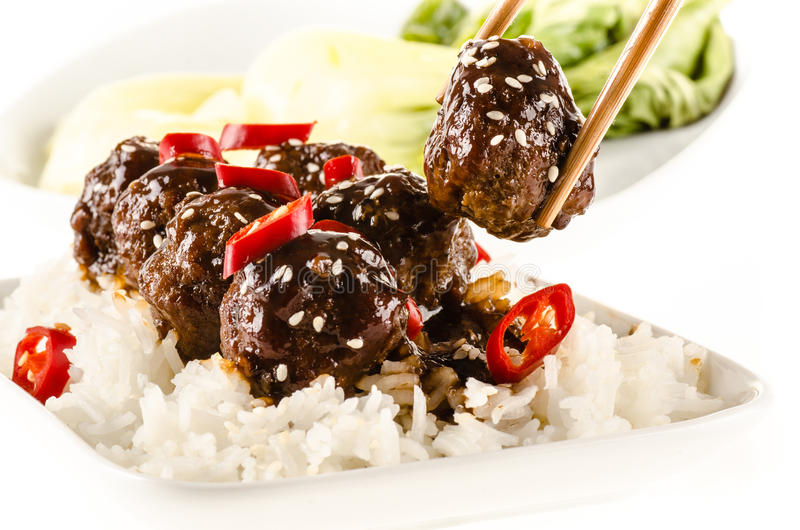 Asian meatballs with chinese sauce served with rice. Steamed bok choy, sesame seeds and chili royalty free stock photo