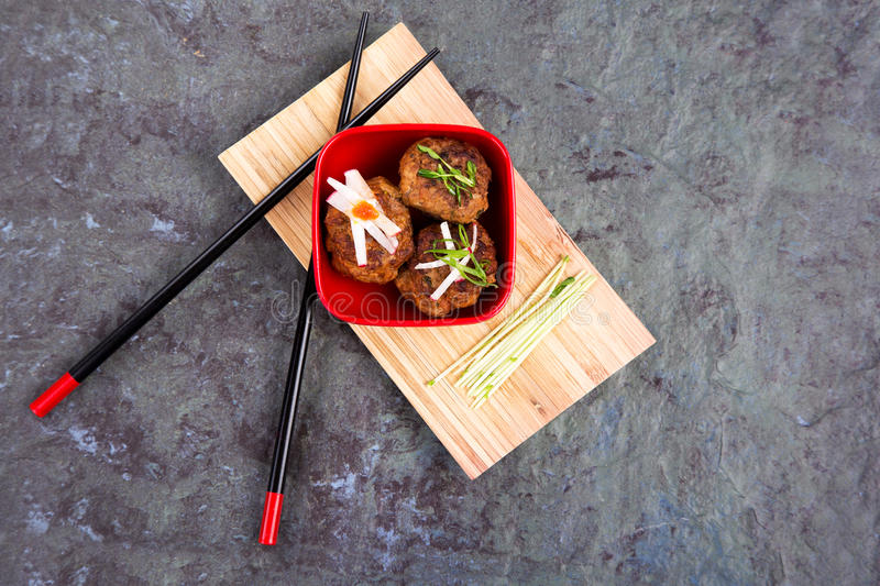 Asian meatballs 1. Asian meatballs, garhished with pea shoots and radish julienne, in a red bowl on bamboo tray with chopsticks, against natural slate background royalty free stock photos