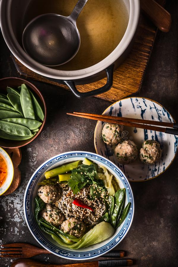 Asian meatballs noodle soup in bowl with chopsticks served on dark rustic background, top view. Asian cuisine concept. Asian meatballs noodle soup in bowl with stock images
