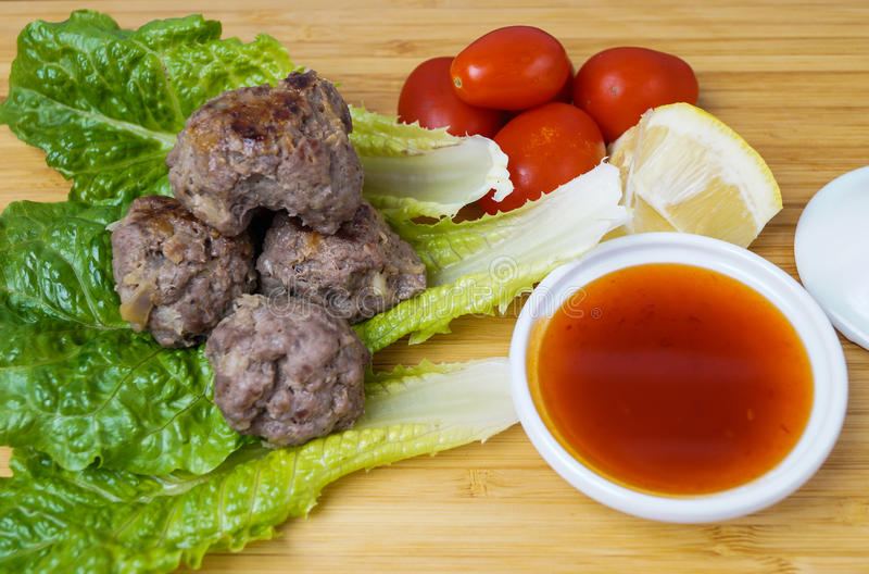 Asian meatballs with sauce. Asian meatballs with sweet and sour sauce and lemon stock image