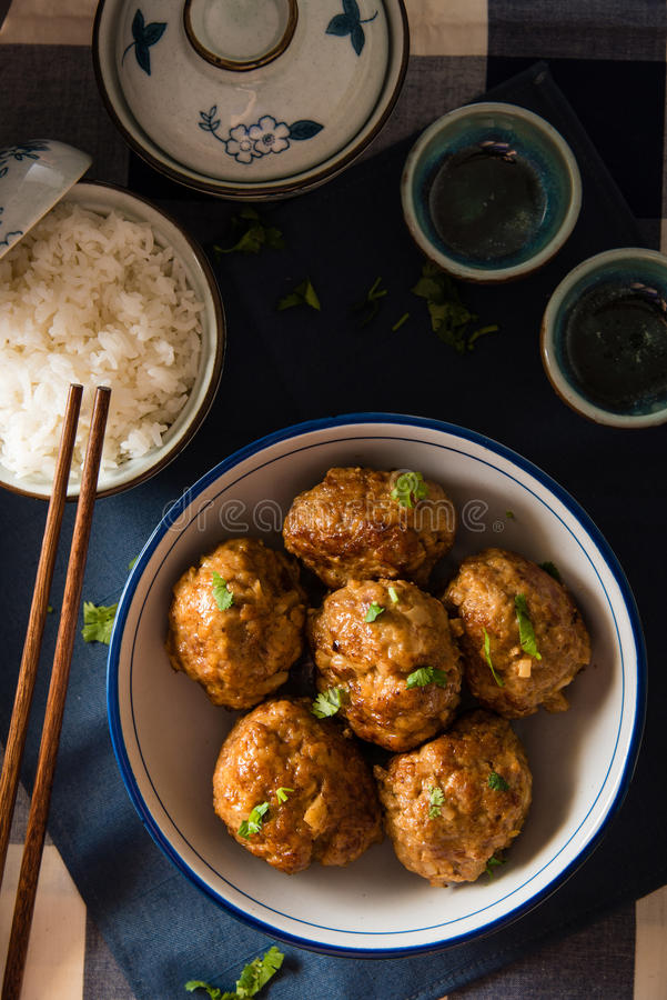 Asian Meatballs Served with White Rice. Asian Meatballs placed in a big bowl, served with white rice royalty free stock images
