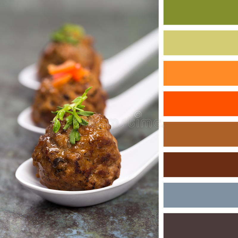Asian meatballs in spoons palette. A trio of Asian meatballs in white ceramic spoons, garnished with peppers and pea shoots. in a colour palette with royalty free stock photography