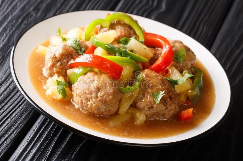 Asian meatballs stewed with fresh pineapples and bell pepper in sweet and sour sauce close-up on a plate. horizontal. Asian meatballs stewed with fresh stock images