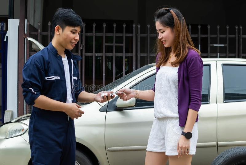 An asian mechanic is receiving cash from customer royalty free stock photos