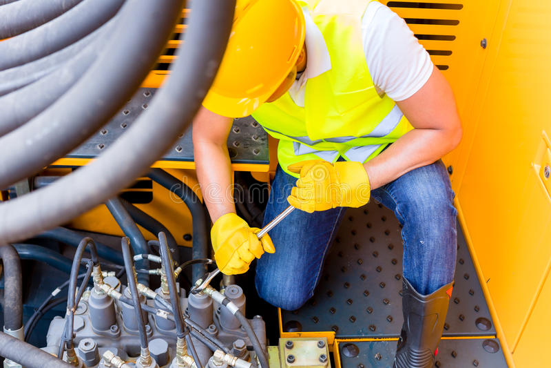 Asian mechanic repairing construction vehicle stock image