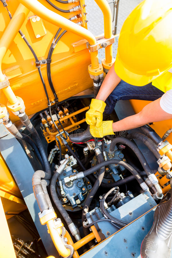 Asian mechanic repairing construction vehicle royalty free stock images