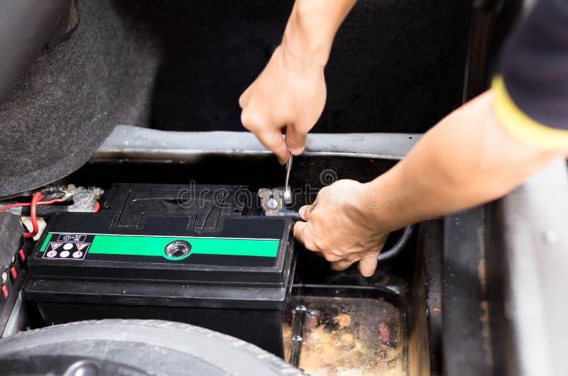 Asian mechanic replacing a car battery stock photography