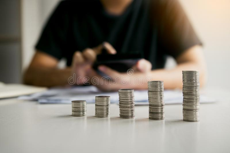 Asian men are calculating about finances about the cost or future investment at home while the coins are arranged with the idea of royalty free stock photo