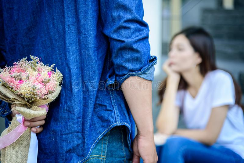 Asian man has preparing and waiting with flower for say sorry an. Asian men has preparing and waiting with flower for say sorry and apologies to girlfriend royalty free stock images