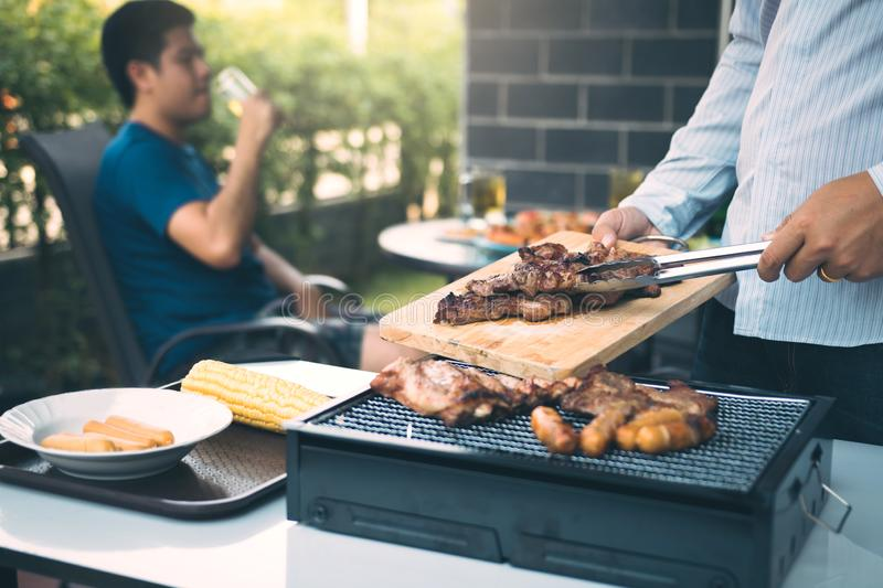 Asian men are pinching pork on a wooden cutting board and holding it to friends who are celebrating in the back.  royalty free stock image