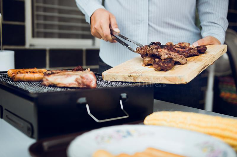 Asian men are pinching pork on a wooden cutting board and holding it to friends who are celebrating in the back royalty free stock images