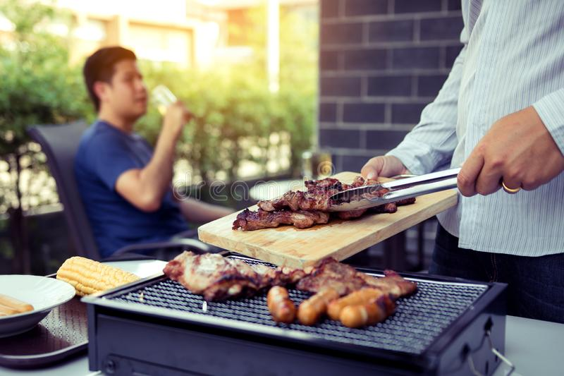 Asian men are pinching pork on a wooden cutting board and holding it to friends who are celebrating in the back stock image