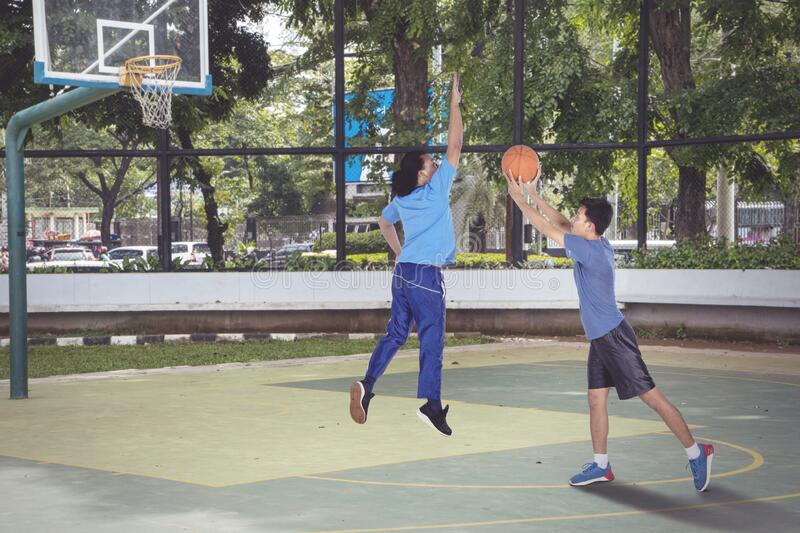 Asian men playing basketball together actively stock photo