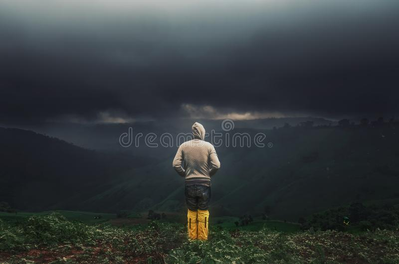 Asian men stand looking at the mountains at rain clouds . stock photography