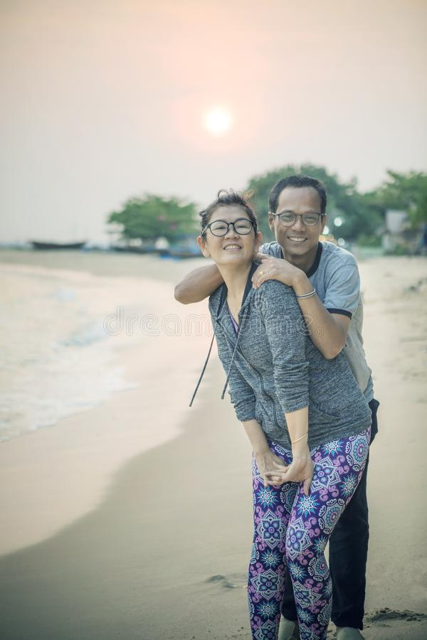 Asian man and woman happiness emotion on vacation sea beach with royalty free stock photography