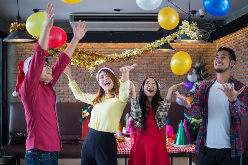 Asian man and woman having fun in Christmas party, dancing and playing balloons at the restaurant. Asian men and women having fun in Christmas party, dancing and royalty free stock image