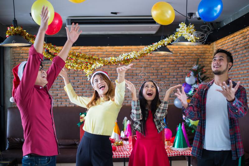 ASian man and woman wear santa claus hat having fun in Christmas party,dancing and playing balloons at the restaurant, royalty free stock photography