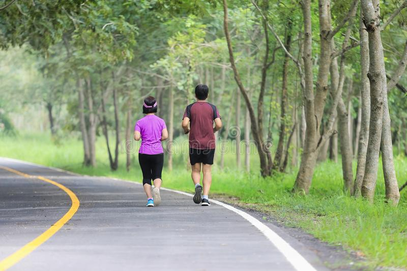 Asian middle aged couple jogging and running in park royalty free stock images