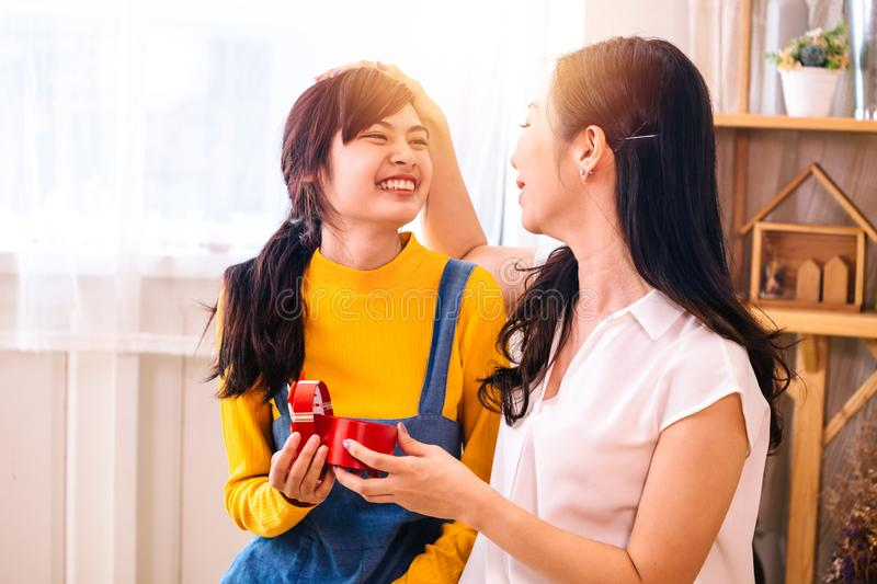 Asian middle-aged mother touching Smiling happy Asian teenage daughter in indoor living room at home royalty free stock photos
