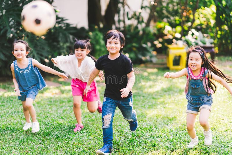 Asian and mixed race happy young kids running playing football together in garden. Multi-ethnic children group, outdoor exercising stock photo
