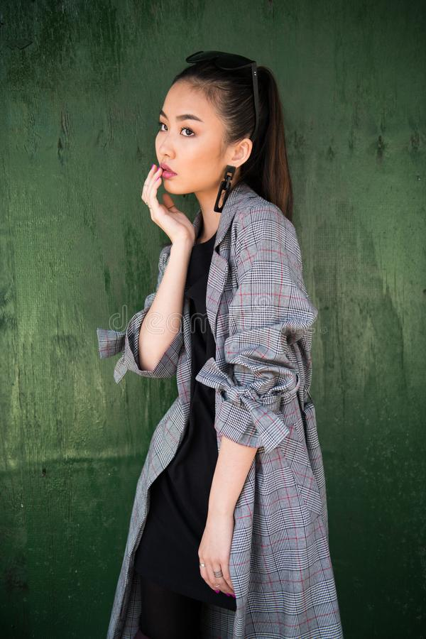Asian model girl posing wearing casual stylish outfit near wooden green wall. stock photos