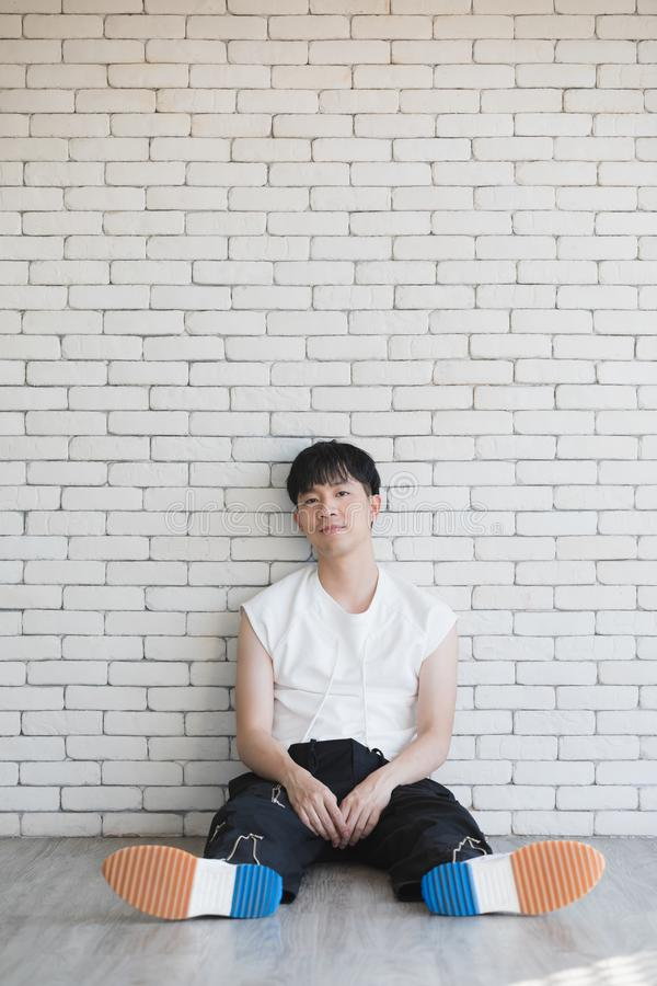 Asian model man sitting on floor and knee up royalty free stock photography