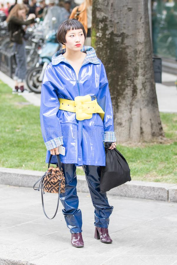Asian model wearing a pair of blue polishing rubber trousers an electric blue coat in shiny rubber with a striking yellow belt royalty free stock photography