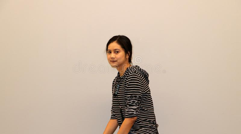 Asian modern woman in white and black stripes color of long-sleeved T-shirt, turned 45 degrees. On grey background royalty free stock images