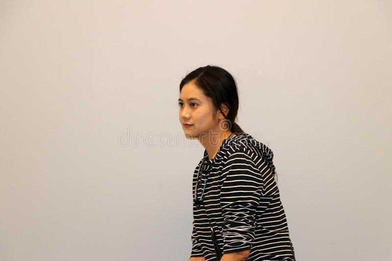 Asian modern woman in white and black stripes color of long-sleeved T-shirt, turned 45 degrees. On grey background stock photo