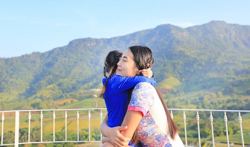 Asian mom cuddle her daughter with love on balcony at hillside stock photography